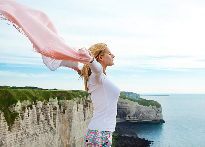 Woman Enjoying Summer Breeze on the Cliff by the Sea by Mosuno for Stocksy United