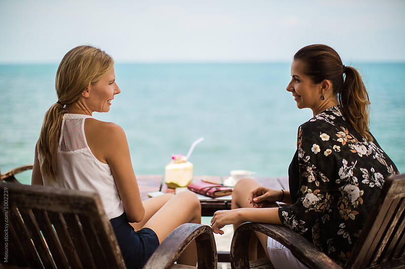 Two Girlfriends Talking at the Beach Cafe by Mosuno for Stocksy United