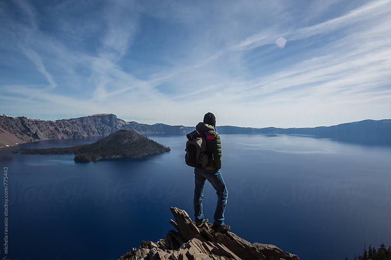 Man looking at the beautiful landscape of Crater Lake by michela ravasio for Stocksy United