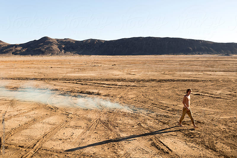 A young shirtless man walking barefoot in the desert by HOWL for Stocksy United