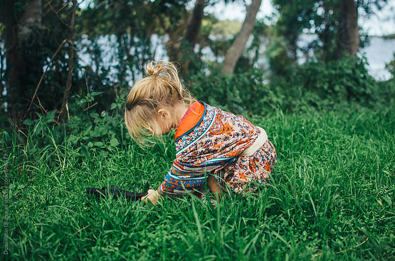 Little girl picking flowers by Dominique Chapman for Stocksy United