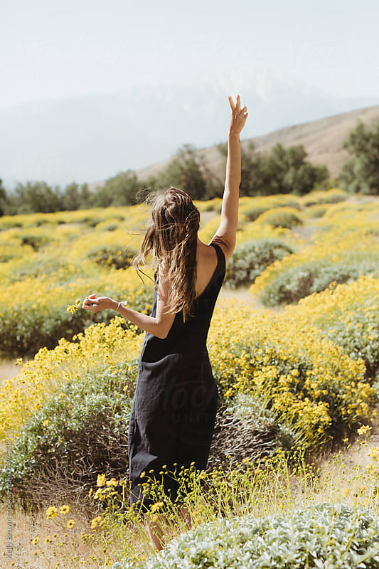 a woman in a field of yellow wild flowers holding up a peace sign in the desert with mountains in the background