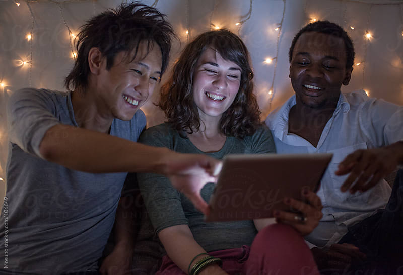 Friends Using Computer Tablet on a Christmas Night by Mosuno for Stocksy United