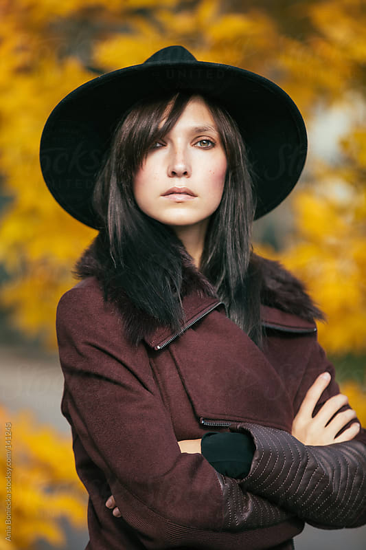 A portrait of a beautiful stoic woman crossing her arms in a burgundy wool jacket by Ania Boniecka for Stocksy United