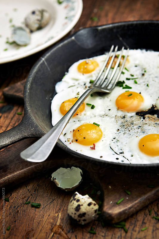 Fried quail eggs in a pan by James Ross for Stocksy United