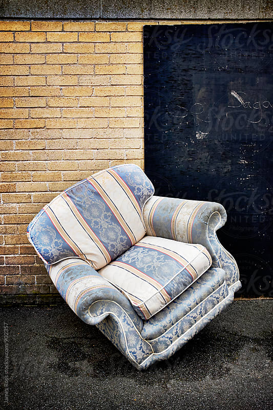 An abandoned armchair by a wall by James Ross for Stocksy United