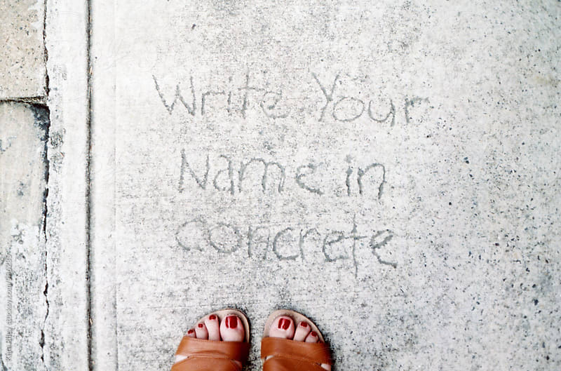 Writing in concrete by Kara Riley for Stocksy United