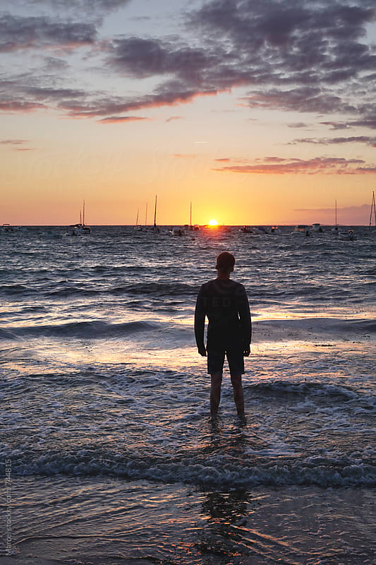 Young man standing in sea at sunset by Marcel for Stocksy United