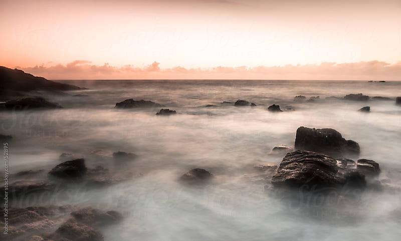 Ocean with rocks at sunset by Robert Kohlhuber for Stocksy United