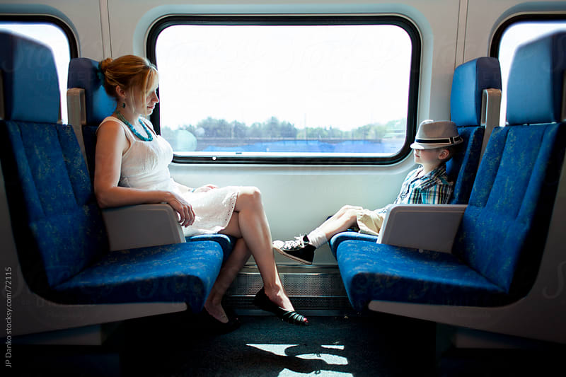 Attractive Mother with Little Boy Relaxing on Commuter Train by JP Danko for Stocksy United