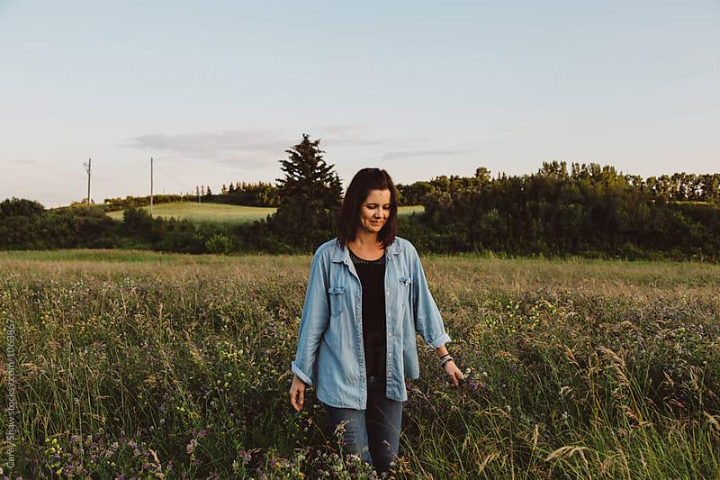 Happy woman walking through farmers field by Carey Shaw for Stocksy United