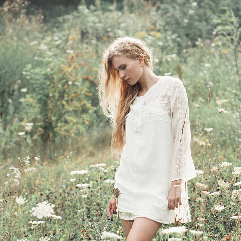 beautiful young blond woman in a field of flowers by Andrei Aleshyn for Stocksy United
