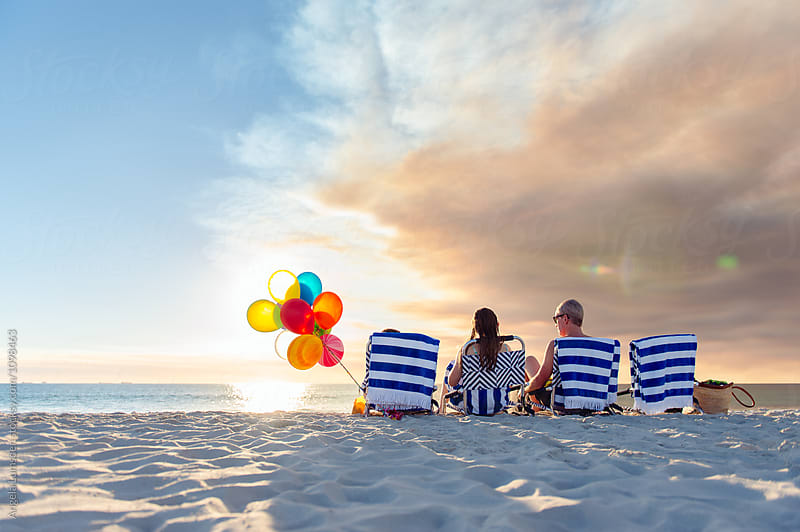 Family sitting on beach chairs at the beach at sunset by Angela Lumsden for Stocksy United