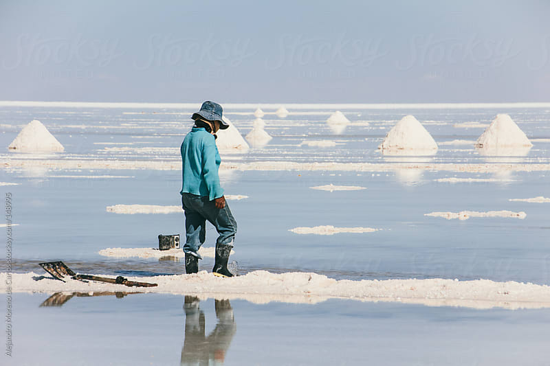 Woman worker working on salt flat in Uyuni, Bolivia by Alejandro Moreno de Carlos for Stocksy United