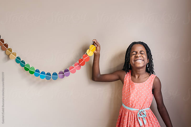 Silly black girl with Easter egg banner by Gabriel (Gabi) Bucataru for Stocksy United