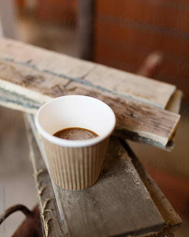 Close up of coffee in paper cup on wood boards on working site by Laura Stolfi for Stocksy United