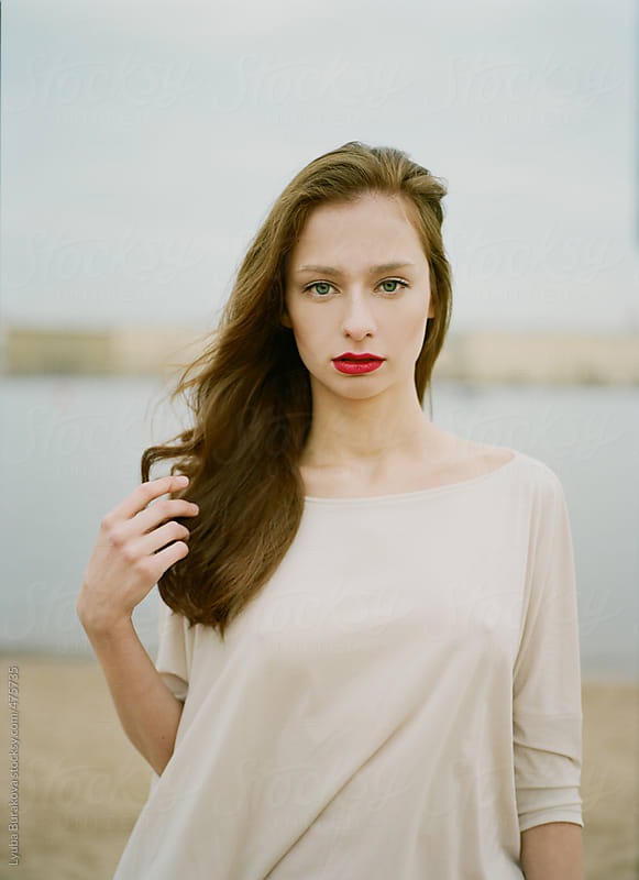Portrait of the beautiful woman with red lips looking at camera by Lyuba Burakova for Stocksy United