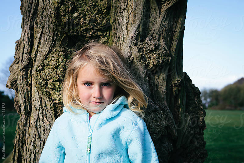 Portrait of serious four year old girl outdoors, standing in front of tree by Paul Edmondson for Stocksy United