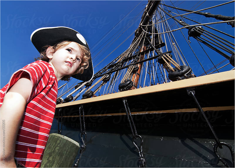 Boy dressed as pirate pretends as he prepares to board his ship by Cara Dolan for Stocksy United