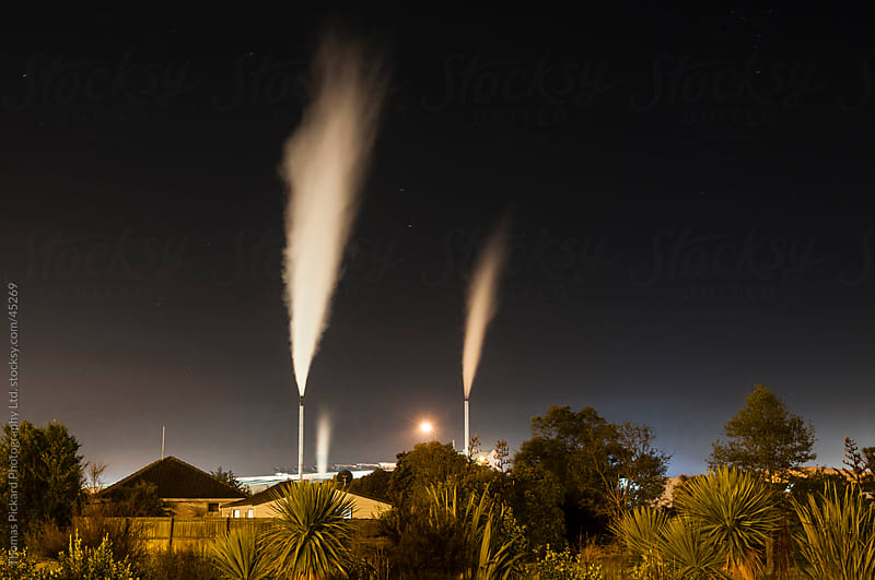 Industrial chimney stacks and suburban housing, New Zealand. by Thomas Pickard for Stocksy United