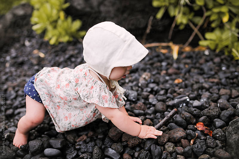 Baby crawling on black rocky beach by Treasures & Travels for Stocksy United