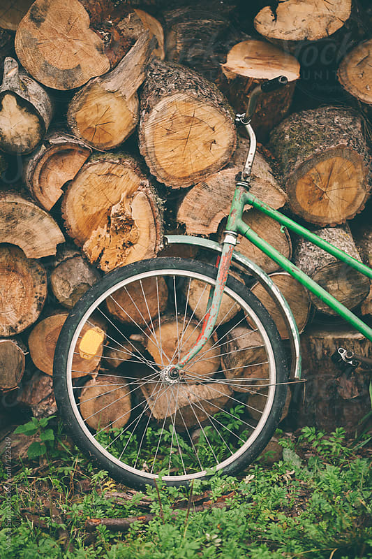 Bicycle parked next to pile of woods. by Marija Savic for Stocksy United