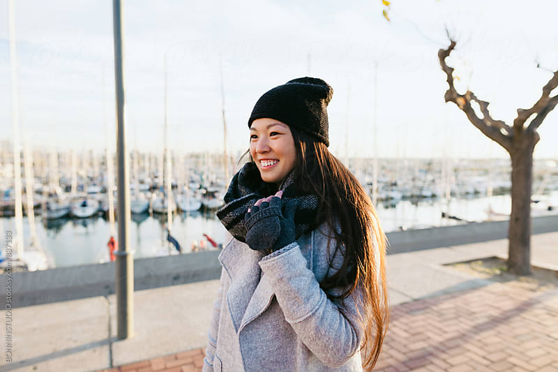 Smiling woman walking by the seaport on winter day. by BONNINSTUDIO for Stocksy United