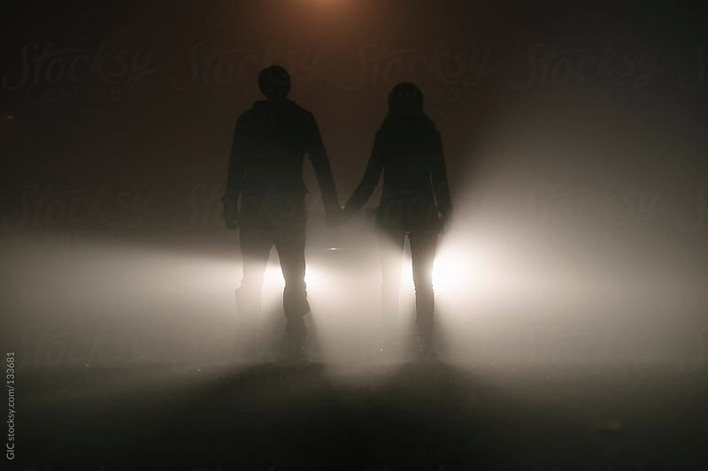 Couple standing in the fog against car lights  by GIC for Stocksy United