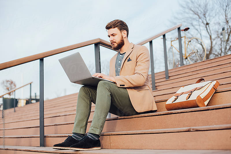 Young Businessman Using a Laptop Outdoors by Lumina for Stocksy United