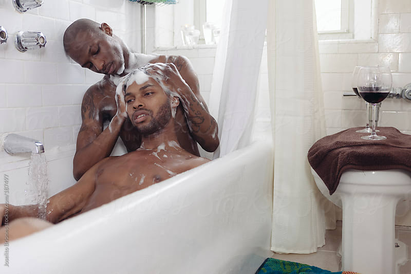 Gay Man Shampooing Partner's Hair while Bathing Together in a Bath Tub by Joselito Briones for Stocksy United