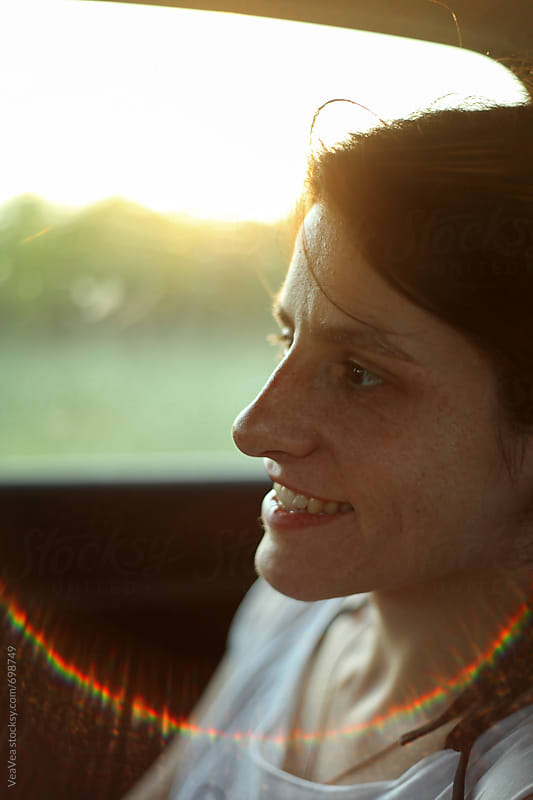 Young happy woman with freckles in a car  by VeaVea for Stocksy United