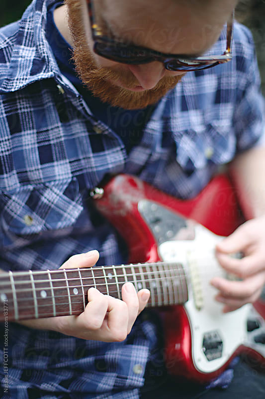 close up of man playing guitar by Natalie JEFFCOTT for Stocksy United