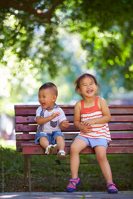 two lovely kids sitting on the bench in the park by cuiyan Liu for Stocksy United
