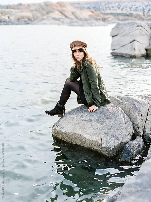 Woman sitting on rock at lake by Daniel Kim Photography for Stocksy United
