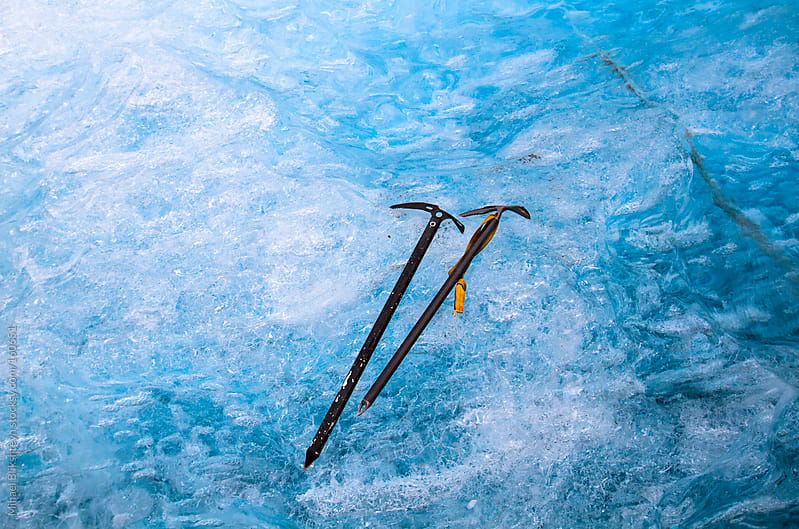 Two ice axes lying against blue ice of an iceberg by Mihael Blikshteyn for Stocksy United