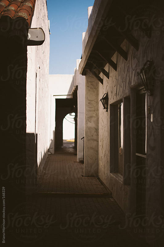 A Shadowed Path Between Spanish Buildings with Doorway by Briana Morrison for Stocksy United