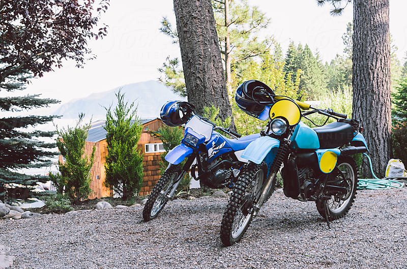 Two motorbikes on gravel by lake by Trent Lanz for Stocksy United