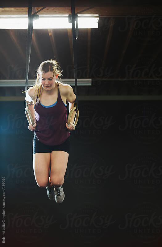 Young, fit woman working out on rings in crossfit gym by Rob and Julia Campbell for Stocksy United