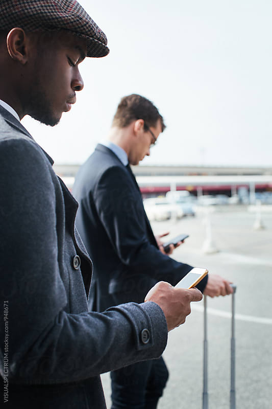 Black and Caucasian Business Travelers Using Smartphones as They Wait For Taxi by Julien L. Balmer for Stocksy United