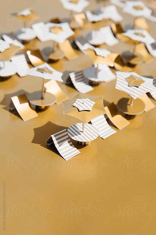 Beach chairs on golden seashore made of paper by Beatrix Boros for Stocksy United