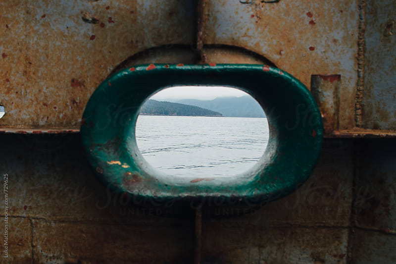 Ferry Porthole View Of Distant Islands Across Ocean Water by Luke Mattson for Stocksy United