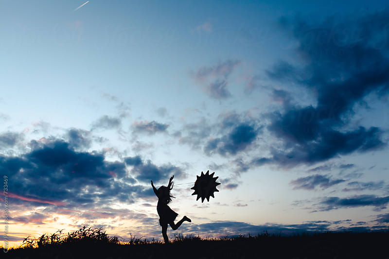 Silhouette of a little girl with a sun balloon by Cindy Prins for Stocksy United
