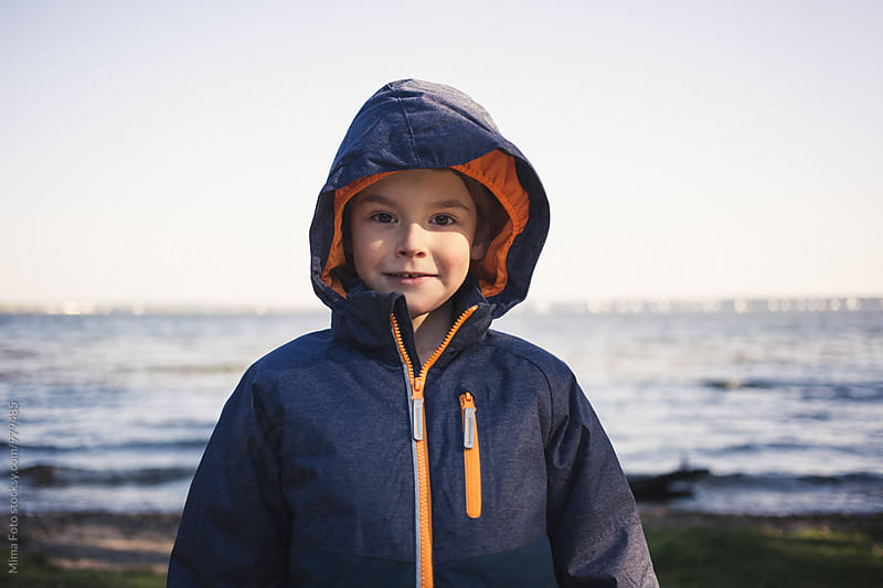Boy in coat standing at lake by Mima Foto for Stocksy United