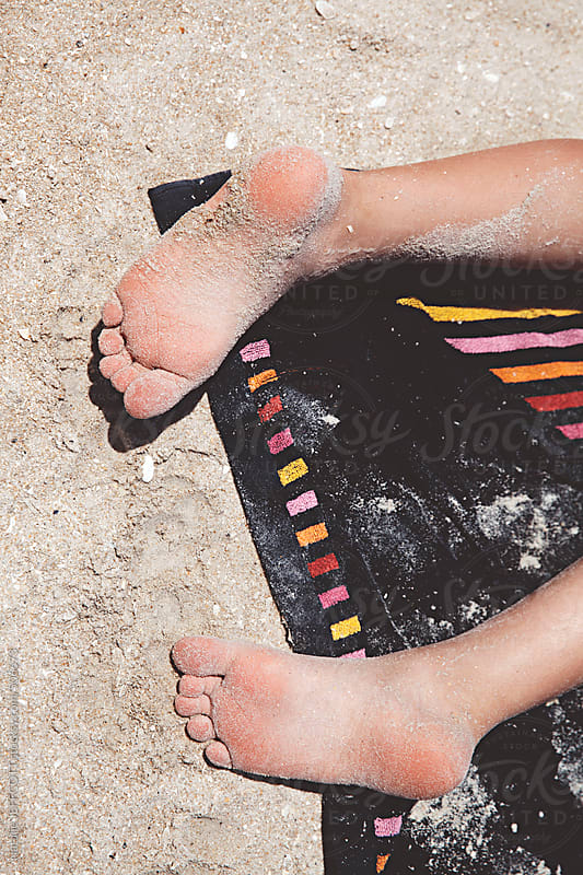 child's feet covered with sand at the beach on a towel by Natalie JEFFCOTT for Stocksy United