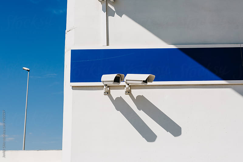 Two digital cameras on building wall by Javier Díez for Stocksy United