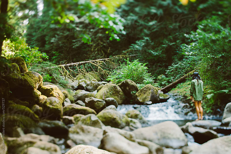 Woman surrounded by beautiful forest and water by Kristine Weilert for Stocksy United