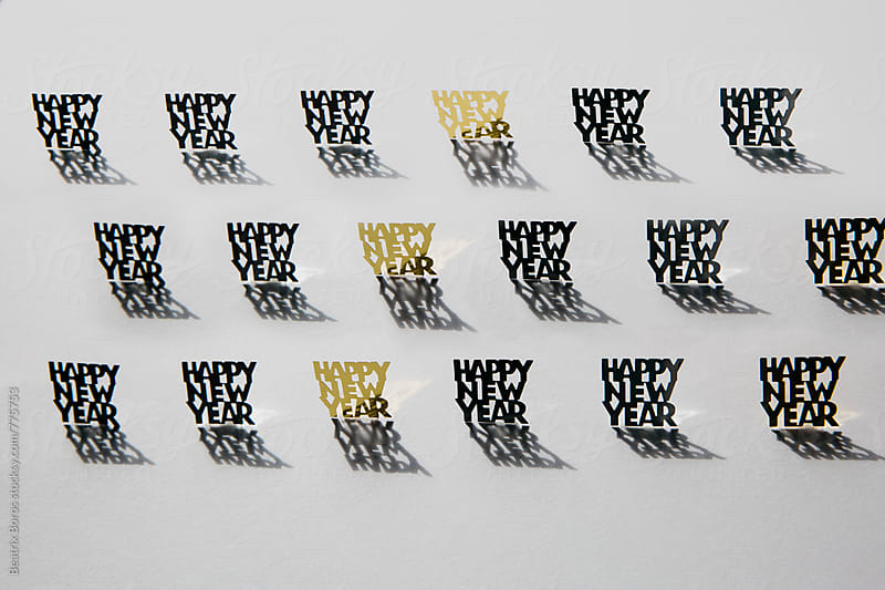 Happy new year shiny glitter confetti in 3 rows on white background by Beatrix Boros for Stocksy United