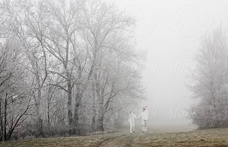 Mother and daughter walking hand by hand in the distant on a foggy Winter day by Beatrix Boros for Stocksy United