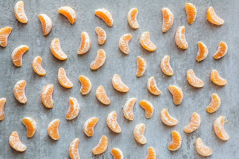 Orange segments on grey background by Nadine Greeff for Stocksy United