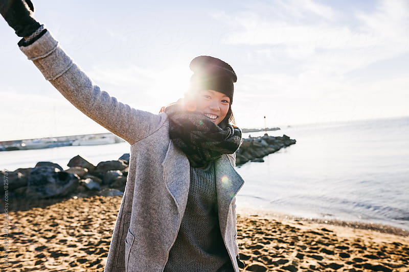 Chinese woman enjoying a sunny winter day on the beach. by BONNINSTUDIO for Stocksy United